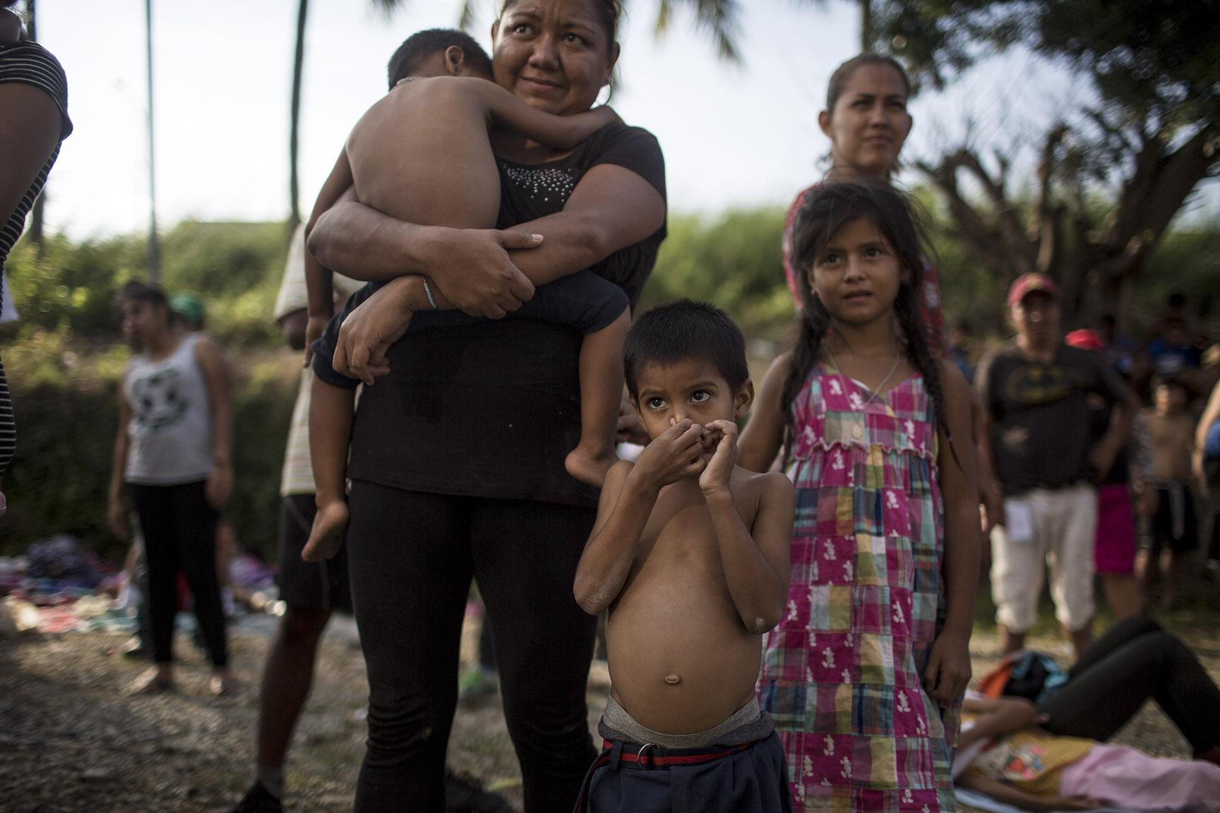 Jotehb, 5, junto con su mamá y dos hermanos, originarios de Villanueva, Honduras. Se tapa la nariz para no respirar los gases de la fumigación / Simone Dalmasso