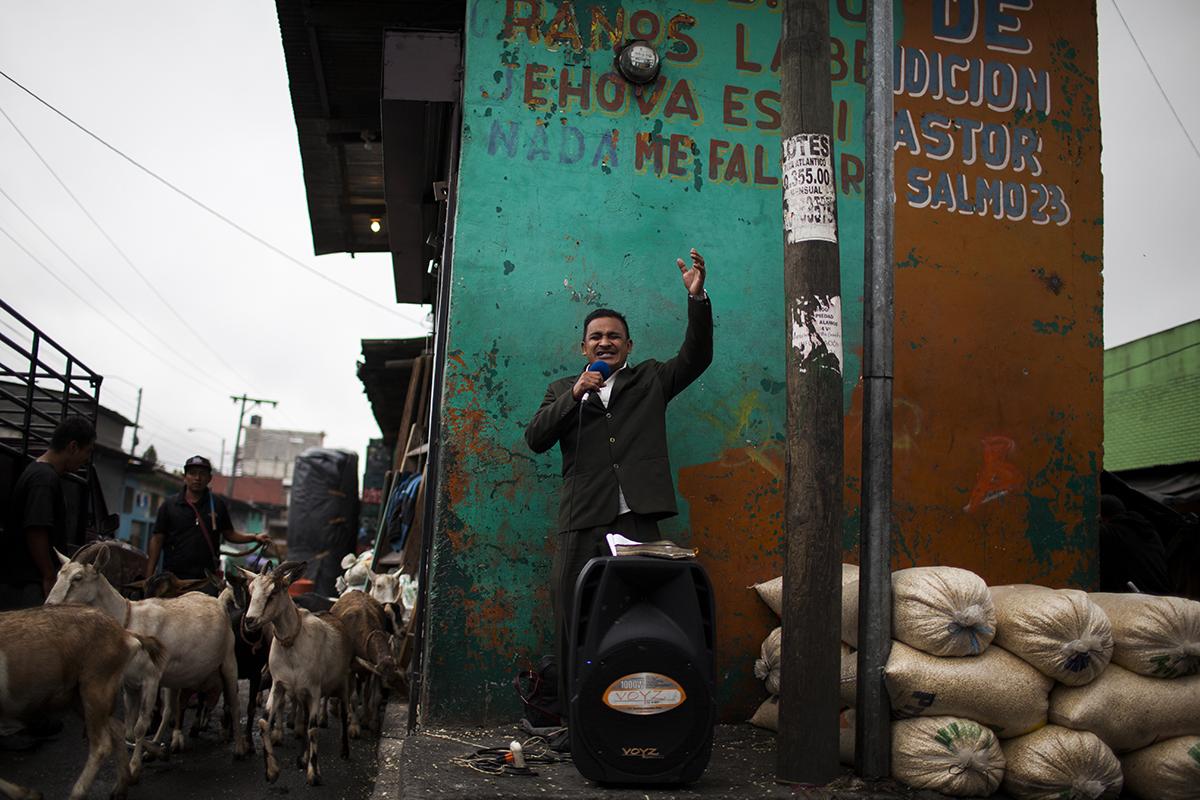 Un pastor evangélico lleva a cabo su sermón entre costales de maíz y cabras