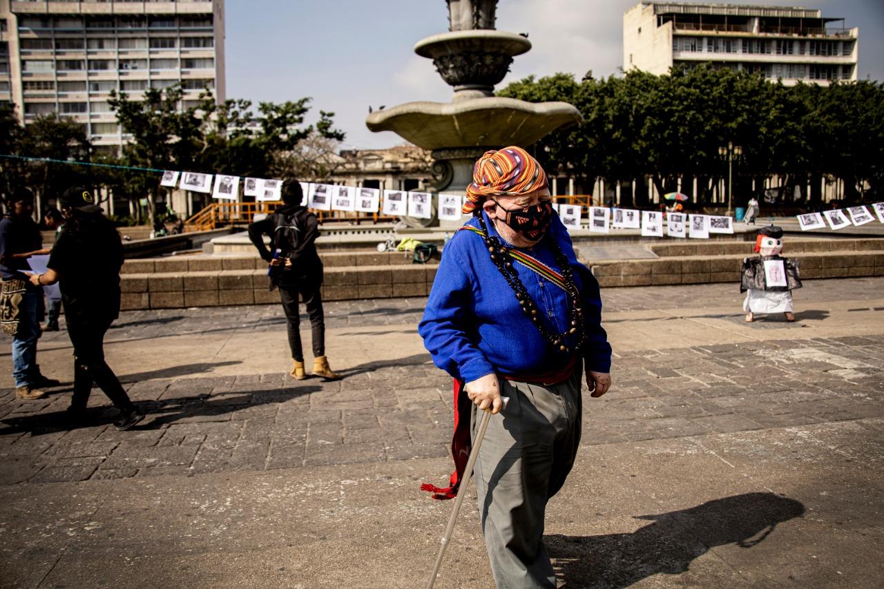 Ponciano López camina frente a los rostros de los diferentes guías espirituales y líderes comunitarios asesinados en los últimos años. El performance fue organizado por estudiantes de la Universidad de San Carlos.